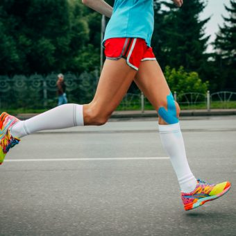 Omsk, Russia - September 20, 2015: girl athlete running a marathon, knees in blue kinesiology taping during Siberian international marathon